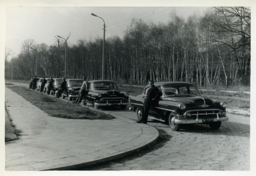 Kolumna samochodów państwowych. Lata 50. Pierwsze dwa auta Chevrolet Bel Air model z 1953 r., drugie dwa radzieckie Wołgi 21, ostanie dwa wozy Warszawy M20. Ustawienie samochodów nie było przypadkowe i odpowiadało randze urzędników danej instytucji najważniejsi jeździli Chevroletami, średni rangą Wołgami, a niżsi rangą krajowymi Warszawami