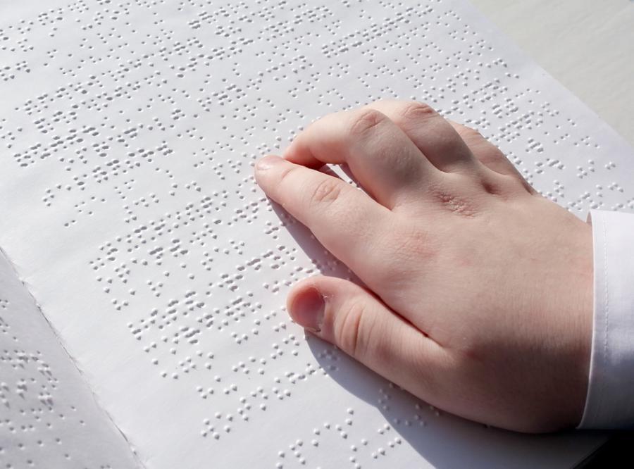 Dziecko czyta książkę zadrukowaną pismem Braille\'a