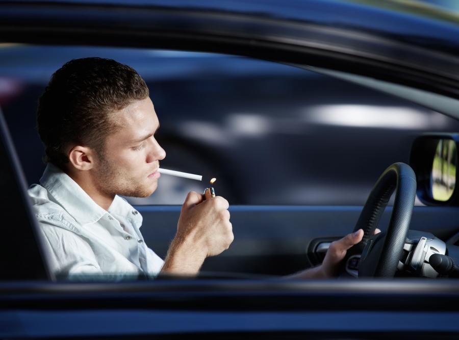 Mężczyzna pali papierosa w samochodzie