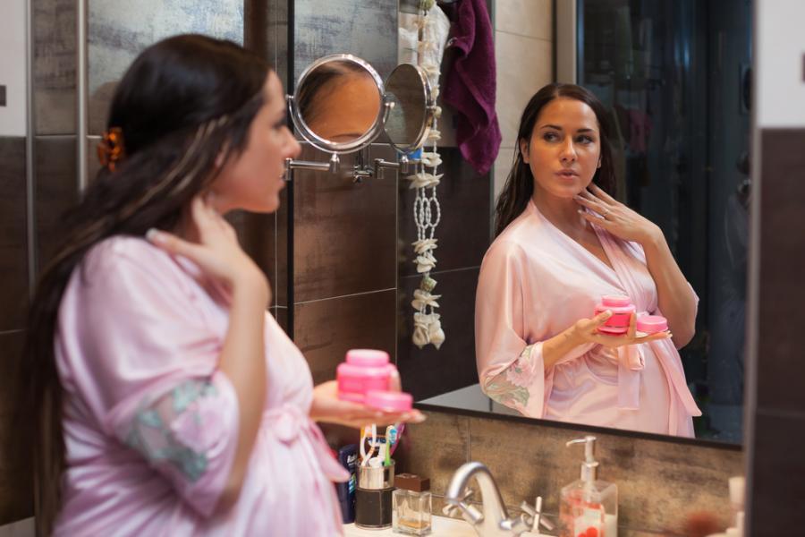 Ciężarna kobieta przed lustrem
