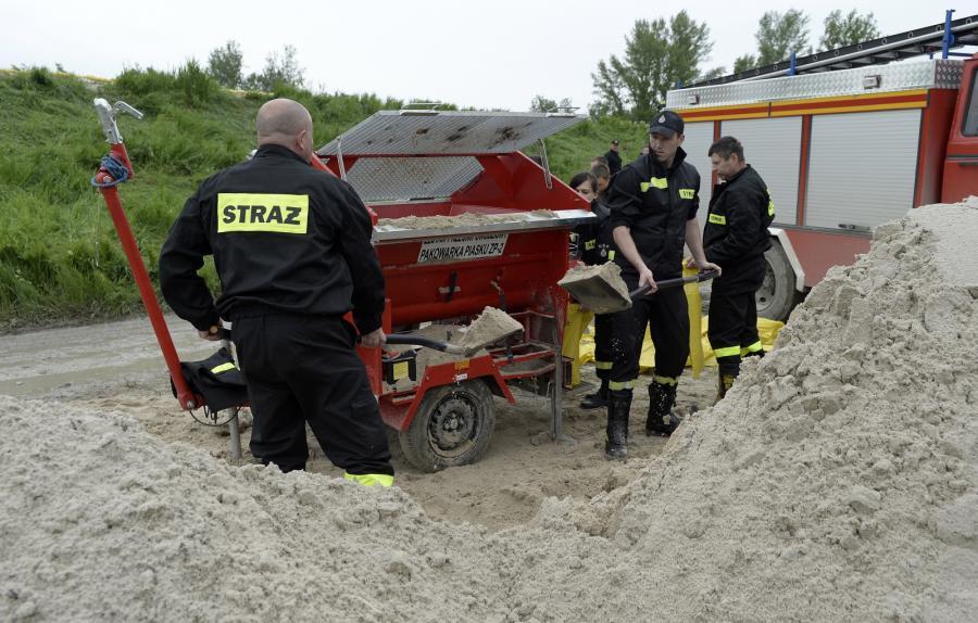 Strażacy napełniają piaskiem worki, które zostaną ułożone na koronie wału przeciwpowodziowego w delcie Wisły i Sanu we Wrzawach
