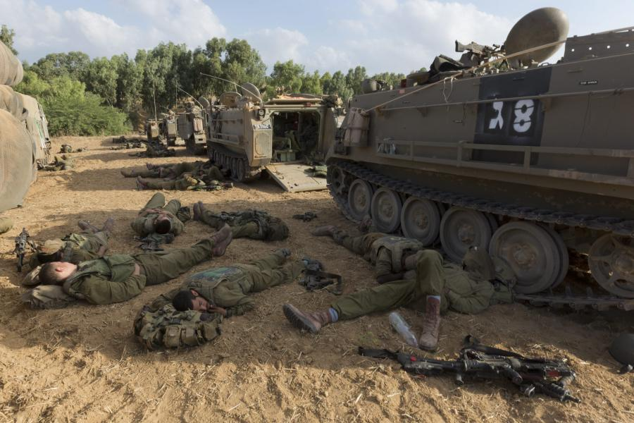 Izraelscy żołnierze śpią przy transporterze opancerzonym