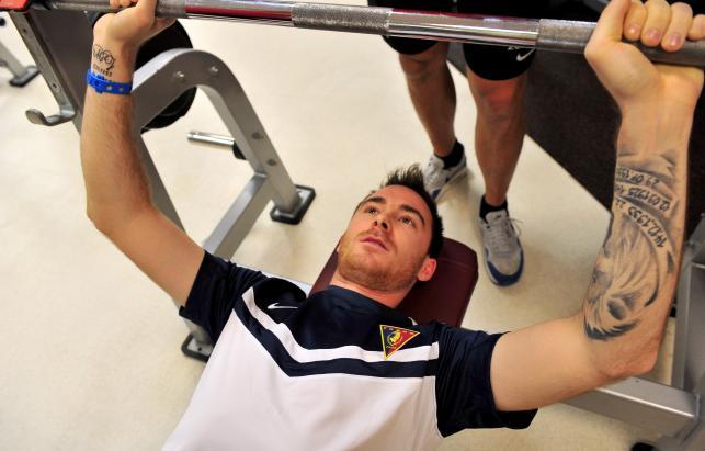 Piłkarz Pogoni Michał Janota podczas ćwiczeń na siłowni