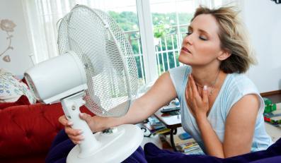 Kobieta chłodząca się wiatrakiem