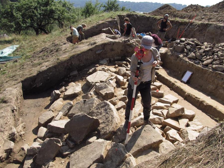 Pomiary w miejscu, gdzie na zewnątrz podstawy muru oporowego znaleziono części zsuniętej po stoku, przewróconej na bok ściany zewnętrznej muru (fot. M. Przybyła)