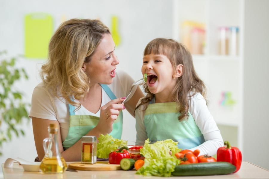 Matka karmiąca córkę warzywami