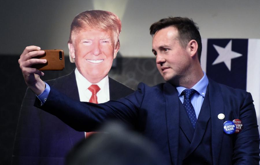 Wybory prezydenckie w USA. Mężczyzna robi sobie zdjęcie z fotografią Donalda Trumpa