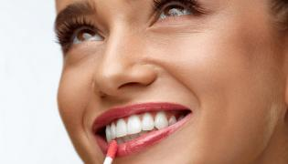 Kobieta nakłada błyszczyk na usta